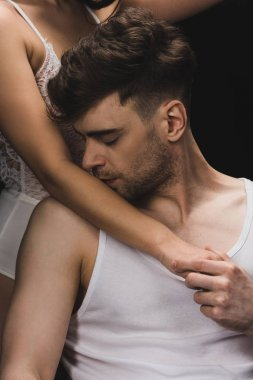 cropped view of woman in white lingerie near handsome man kissing her hand isolated on black