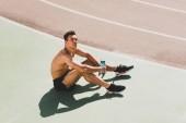 unavený sportovec se smíšeným závodem sedícího na stadionu