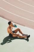 sportivo da corsa mista seduto allo stadio e acqua potabile