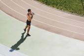 Režie na smíšený závodní sportovec držící ručník a pitnou vodu na stadionu