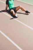 Fotografie abgeschnittene Ansicht von müden Sportlern im Stadion sitzen