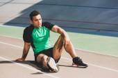 Fotografie unavený sportovec se smíšeným závodem sedícího na stadionu