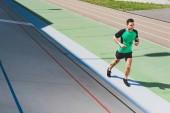 kompletní pohled na smíšenou sportovní sportovce běžící na stadionu