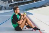 pohled na smíšené sportovní sportovce sedící v relaxační formě na běžícím kolejích a pohled na zelené jablko