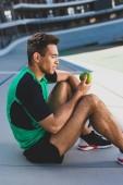 pohled na smíšené sportovní sportovce sedící na běžícím kolejích a pohled na zelené jablko