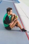 sportovní sportovec sedící na běžícím kolejích a držící zelený jablko