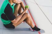 oříznutý pohled sportovce sedící na běžícím kolejích a držící zelený jablko