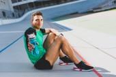 Fotografie sportovní sportovec sedící na trati na stadionu, hledaje láhev s vodou na kameře