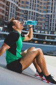Photo mixed race sportsman sitting on running track at stadium and drinking water from blue bottle