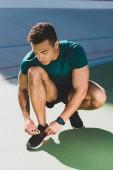 vista a tutta lunghezza dello sportivo allacciatura scarpe da ginnastica allo stadio
