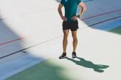 oříznutý pohled sportovce stojící s rukama v bocích na stadionu