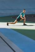 sportovní sportovec na stadionu, stojící na zeleném patře na slunci
