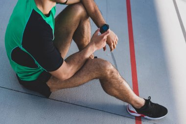 cropped view of mixed race sportsman using smartwatch at running track