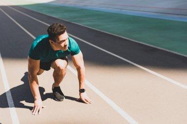 mixed race sportsman on start position looking away at stadium
