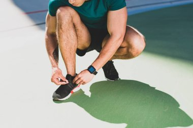 cropped view of sportsman lacing up sneakers, standing on green floor