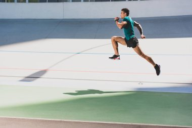 side view of mixed race sportsman running at stadium