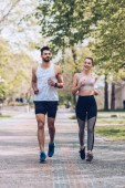 smiling sportsman and sportswoman running along wide alley in park