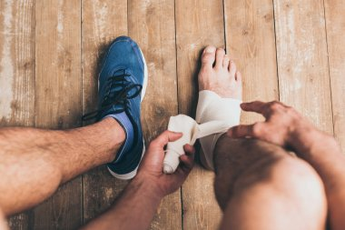 cropped view of sportsman in one sneaker bandaging injured leg with elastic bandage
