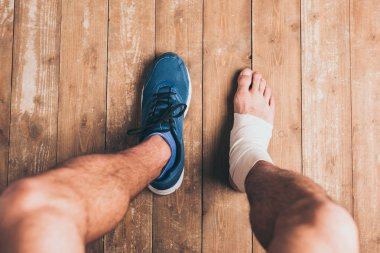 cropped shot of injured sportsman sitting in one sneaker with one foot in elastic bandage
