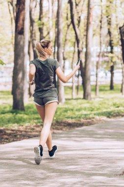 back view of young woman holding smartphone and listening music in earphones while jogging in park