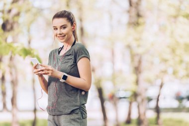 pretty woman in sportswear smiling at camera while holding smartphone and listening music in earphones