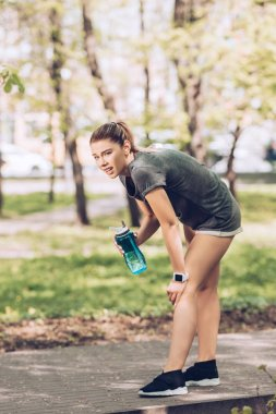 tired thirsty sportswoman looking away while holding sport bottle