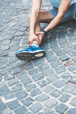 partial view of sportsman touching injured leg while sitting on pavement