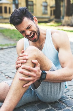 young sportsman suffering from pain and screaming while sitting on pavement and touching injured leg