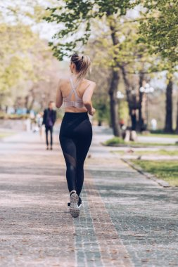 back view of young sportswoman jogging along wide walkway in park