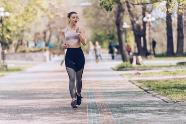 attractive sportswoman jogging along wide alley in green park
