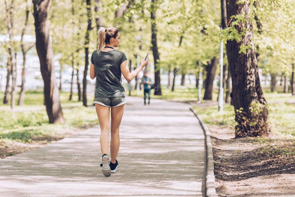 back view of young sportswoman jogging in park while holding smartphone and listening music in earphones