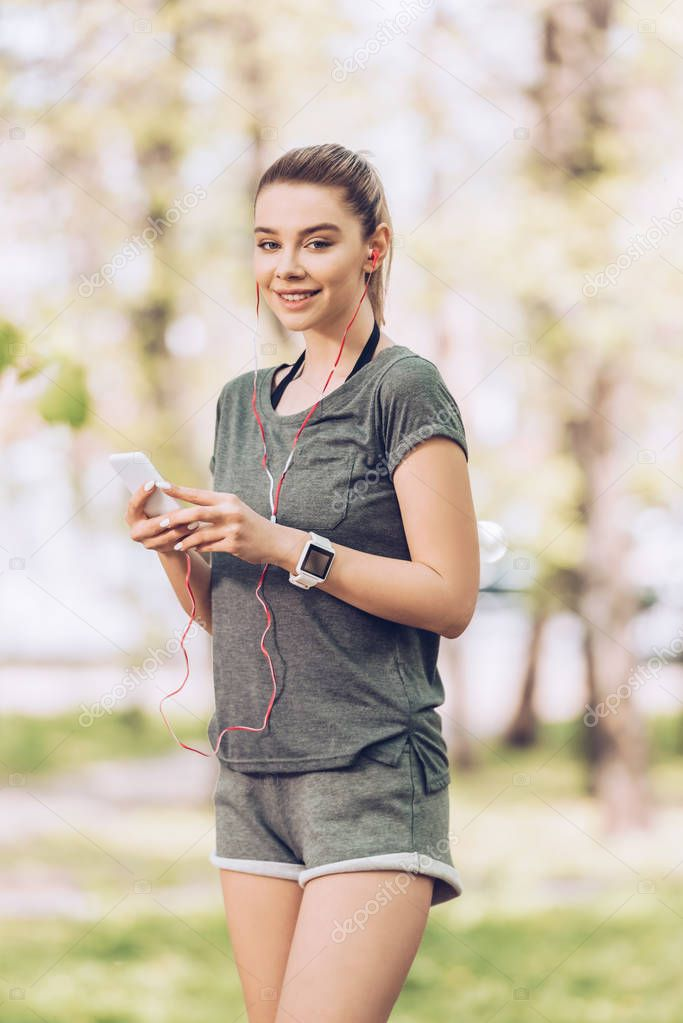attractive woman in sportswear using smartphone and listening music in earphones while smiling at camera