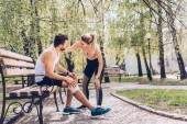young sportswoman standing near injured sportsman sitting on bench in park