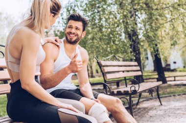 injured sportsman smiling and showing thumb up while sitting on bench near young sportswoman