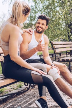 injured sportsman smiling and showing thumb up while sitting on bench near sportswoman