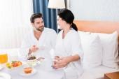 Selektiver Fokus glücklicher Männer und Frauen am Tisch mit Frühstück
