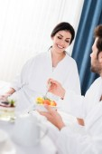 selective focus of happy woman looking at bearded man holding fork near tasty fruit salad
