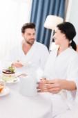 selektiver Fokus der Frau mit der Teekanne und dem Blick auf den Mann