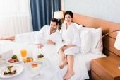 glücklicher Mann und Frau mit Barfuß beim Frühstück im Hotelzimmer