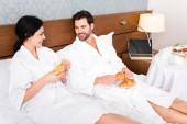 fröhlicher Mann mit Croissants, während er die Frau mit einem Glas Orangensaft ansieht