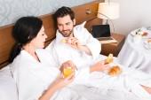 fröhlicher Mann mit Croissant, während er attraktive Frau mit einem Glas Orangensaft ansieht