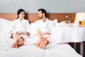 selektivní zaměření šťastného muže a ženy dívali se na sebe blízko stolu se snídaní