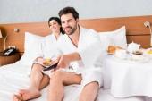 Selektiver Fokus eines glücklichen Mannes mit Fernbedienung in der Nähe einer glücklichen brünetten Frau