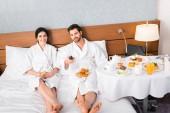 fröhlicher Mann hält Fernbedienung neben Frau mit Glas Orangensaft