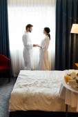 Fotografie selektivní zaměření pohledného vousatého muže, který drží ruce s atraktivní ženou v hotelovém pokoji
