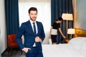 glückliche Empfangsdame steht mit der Hand in der Tasche neben Dienstmädchen im Hotelzimmer