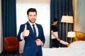 Fotografie selektivní zaměření šťastné recepční ukazující na palec u služky v hotelovém pokoji