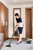 brunette housemaid cleaning carpet with vacuum cleaner in hotel room