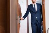 Ausgeschnittene Ansicht eines fröhlichen Mannes, der Türgriff berührt, während er Tür öffnet