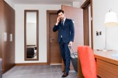 handsome businessman talking on smartphone and standing with suitcase in hotel room